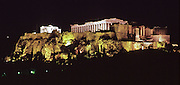The Erechtheion (left) and Parthenon (right) are lit at night atop the Acropolis, in Athens, Greece, Europe. The Parthenon was first built from 447-438 BC, using Pentelic marble plus a wooden roof. The Parthenon is the largest Doric-column temple ever completed in Greece. It was designed as a treasury for tribute money moved from Delos Island and was dedicated to the worship of Athena. A huge, 12-meter tall statue of Athina Polias was placed in 432 BC. The Erechtheion, built entirely of marble in 421-406 BC, is the most sacred sanctuary on the Acropolis. The Acropolis of Athens and its monuments were honored as a UNESCO World Heritage Site in 1987.