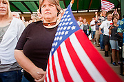 "May 29 - TEMPE, AZ: People sing the Star Spangle Banner at the start of a rally against illegal immigration in Tempe, AZ, Saturday. About 3,000 people attended a ""Buy Cott Arizona"" rally at Tempe Diablo Stadium in Tempe, AZ Saturday night. The rally was organized by members of the Arizona Tea Party movement to show support for Arizona law SB1070. The ""Buy Cott"" is a reaction to the economic boycott planned by opponents of SB1070. SB1070 makes it an Arizona state crime to be in the US illegally and requires that immigrants carry papers with them at all times and present to law enforcement when asked to. Critics of the law say it will lead to racial profiling, harassment of Hispanics and usurps the federal role in immigration enforcement. Supporters of the law say it merely brings Arizona law into line with existing federal laws.  Photo by Jack Kurtz"