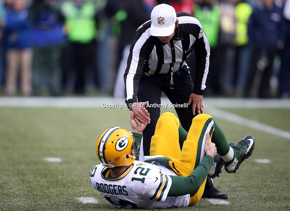 Green Bay Packers quarterback Aaron Rodgers (12) gets help off the ground by referee Tony Corrente (99) as he holds his leg after getting knocked down on a third quarter pass play during the NFL week 20 NFC Championship football game against the Seattle Seahawks on Sunday, Jan. 18, 2015 in Seattle. The Seahawks won the game 28-22 in overtime. ©Paul Anthony Spinelli