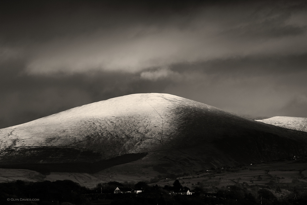 Second snows on the Welsh hills, and a dusted icing across the rounded summit of Moel Eilo, as seem from Anglesey.