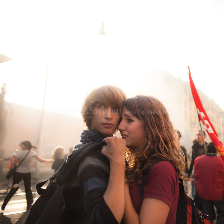 October 15 2011. Rome. Italy.<br /> Teenagers couple looking at the turmoils. <br /> Massive violent protests exploded across Rome amid the country's worst economic crisis.<br /> United for Global Change demonstration.
