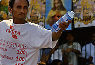 A water vendor with price tage printed on the T-Shirts. The hot temperature makes water an essential item.