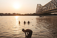Bathers near Howrah Bridge, which spans the Hooghly River in Kolkata.