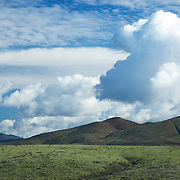 Dramatic cumulus clouds over green fields, springtime, San Diego county.