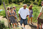 "Carlos Rosario shows the garden at Bard College in Annandale-on-Hudson, New York, to students. He helped creating it after his release from prison in May 2010...Story: The Bard Prison Initiative.Former inmate Carlos Rosario, 35-year-old husband and father of four, was released from Woodbourne Correctional Facility after serving more than 12 years for armed robbery. Rosado is one of the students participating in the Bard Prison Initiative, a privately-funded program that offers inmates at five New York State prisons the opportunity to work toward a college degree from Bard College. The program, which is the brainchild of alumnus Max Kenner, is competitive, accepting only 15 new students at each facility every other year. .Carlos Rosario received the Bachelor of Arts degree in social studies from the prestigious College Saturday, just a few days after his release. He had been working on it for the last six years. His senior thesis was titled ""The Diet of Punishment: Prison Food and Penal Practice in the Post-Rehabilitative Era,"".Rosado is credited with developing a garden in one of the few green spaces inside the otherwise cement-heavy prison. In the two years since the garden's foundation, it has provided some of the only access the prison's 800 inmates have to fresh vegetables and fruit...Rosario now works for a recycling company in Poughkeepsie, N.Y...Photo © Stefan Falke"