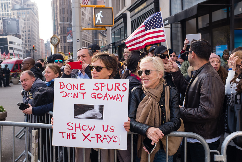 "New York, NY - 11 November 2019. New York City's Veterans Day Parade, today marking the 100th anniversary of the armistice ending the fighting of the first World War, was attended by a number of people protesting President Trump, who spoke at the opening ceremony, and a smaller number of pro-Trump supporters. A woman has a sign reading ""Bone Spurs don't go away / show us the x-rays."""