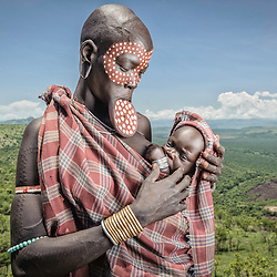 Mursi woman with a lip plate holding her child on a lookout of the Omo valley, Ethiopia