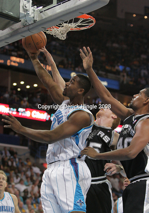 17 December 2008: New Orleans Hornets center Hilton Armstrong (12) shoots over San Antonio Spurs defenders Matt Bonner (15) and Kurt Thomas (40) during a NBA regular season game between the Western Conference rivals the San Antonio Spurs and the New Orleans Hornets at the New Orleans Arena in New Orleans, LA..