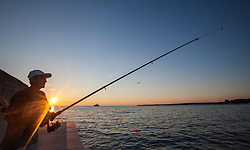 THEMENBILD - URLAUB IN KROATIEN, ein Angler beim fischen bei Sonnenuntergang, aufgenommen am 03.07.2014 in Porec, Kroatien // a fisherman while fishing at sunset at Porec, Croatia on 2014/07/03. EXPA Pictures © 2014, PhotoCredit: EXPA/ JFK