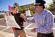 """09 DECEMBER 2010 - PHOENIX, AZ: MITCH RUBIN, right, arrests VICTOR ARONOW, left, who was playing former President George W. Bush in front of the Barnes & Noble Bookstore in Phoenix, AZ, Thursday, Dec. 9. More than 2,000 people lined up starting at 5AM to get copies of the former President's book, """"Decision Points."""" A handful of protesters demonstrated against President Bush near the bookstore, calling him a """"war criminal.""""   PHOTO BY JACK KURTZ"""