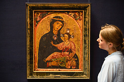 "© Licensed to London News Pictures. 28/06/2019. LONDON, UK. A staff member views ""The Madonna and Child, two angles in the spandrels above"", mid 1230s, by Third Master of Anagni (Est. GBP200-300k) at the preview of Sotheby's Old Masters sale which takes place at its New Bond Street galleries on 3 July.  Photo credit: Stephen Chung/LNP"