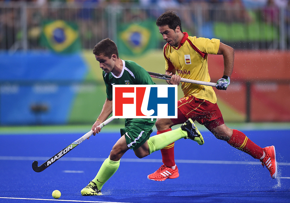 Spain's Miguel Delas (R) chases Brazil's Lucas Paixao during the men's field hockey Spain vs Brazil match of the Rio 2016 Olympics Games at the Olympic Hockey Centre in Rio de Janeiro on August, 6 2016. / AFP / MANAN VATSYAYANA        (Photo credit should read MANAN VATSYAYANA/AFP/Getty Images)