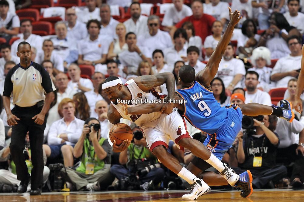 Jun 17, 2012; Miam, FL, USA; Miami Heat small forward LeBron James (6) gets tangled with Oklahoma City Thunder power forward Serge Ibaka (9) during the third quarter in game three in the 2012 NBA Finals at the American Airlines Arena. Mandatory Credit: Derick E. Hingle-USA TODAY SPORTS