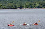 Cornwall-on-Hudson, New York - Three people paddle kayaks on Hudson River on June 20, 2014.