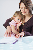 Mother with daughter (3-4) on laps looking at paperwork