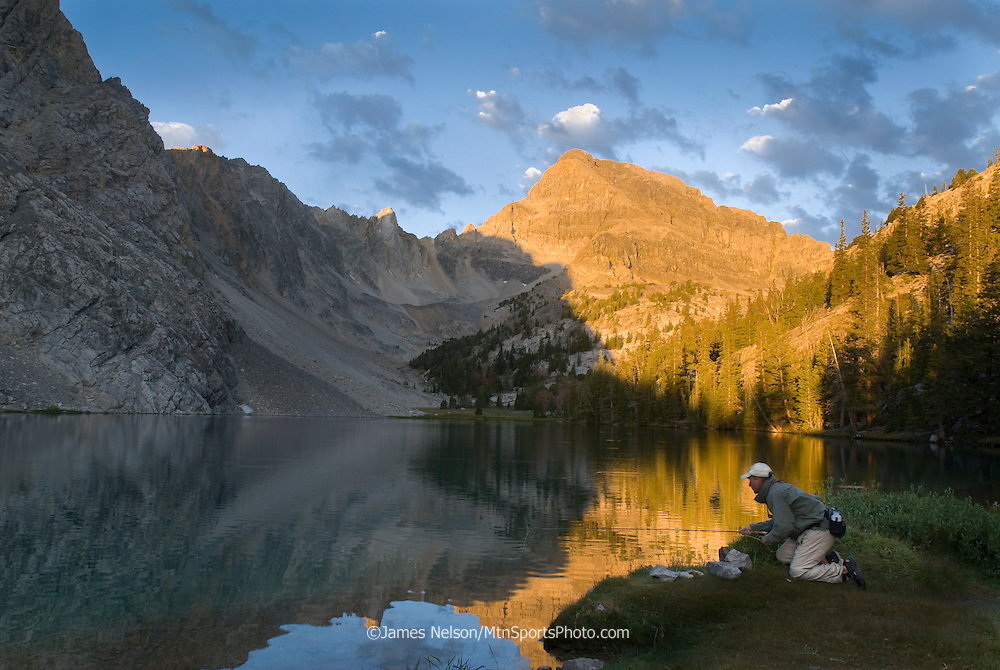 An angler fly fishes for trout at sunrise on an alpine lake in the Lost River Range of Idaho.