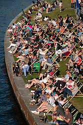 People sitting in afternoon beside River Spree at outdoor bar in Berlin Germany