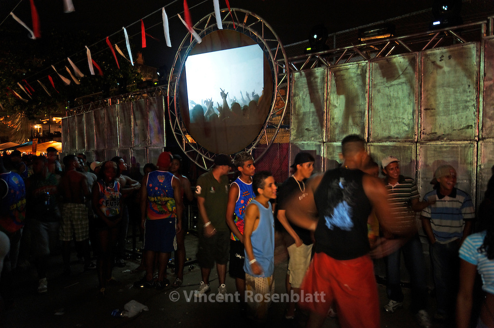 "Projection of the photographic series ""Rio Baile Funk"" during a Baile, here in the favela Vila Cruzeiro, in a giant Baile Funk at the football ""Campo da Ordem""; Complexo da Penha - northern area of Rio de Janeiro. After years documenting and photographing  the bailes funk, it seemed only fair to show this work where it actually took place.."
