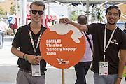 Young attendant of the Holland Pavilion at Expo 2015 hold a sign that reads &quot;Smile! This is a strictly happy zone!&quot;, Rho-Pero, Milan, 2015. &copy; Carlo Cerchioli <br /> <br /> &quot;Sorridi! questa &egrave; una zona rigorosamente felice!&quot; recita il cartello impugnato dai giovani addetti del padiglione Olanda a Expo 2015, Rho-Pero, Milano, 2015.
