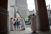 Father Paulo waits to greet worshipers outside the front of the church, Our Lady Of Peace, at Missao Paz, São Paulo, Brazil.<br /> <br /> Missao Paz provides advice and support on employment, health, family, community and education. They also have residential quarters where people can stay when they have no where else. <br /> <br /> Their mission is to welcome, understand, integrate and celebrate the lives of immigrants and refugees, dreaming of a universal citizenship.