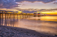 The final minutes of dusk settle over the gulf and pier at Naples beach in Florida.