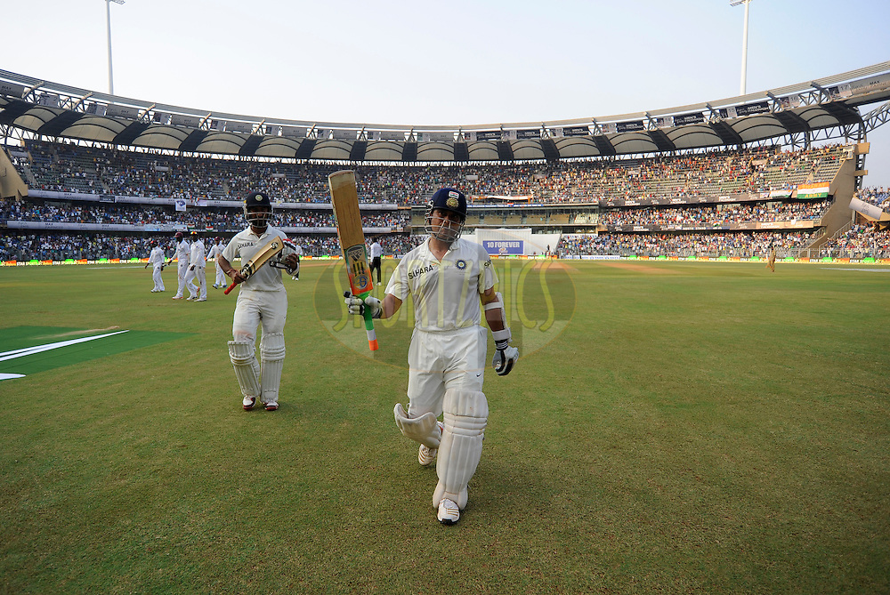 Sachin Tendulkar of India acknowledge the crowd as he walks off the field at the end of days play on day one of the second Star Sports test match between India and The West Indies held at The Wankhede Stadium in Mumbai, India on the 14th November 2013<br /> <br /> This test match is the 200th test match for Sachin Tendulkar and his last for India.  After a career spanning more than 24yrs Sachin is retiring from cricket and this test match is his last appearance on the field of play.<br /> <br /> Photo by: Pal PIllai - BCCI - SPORTZPICS<br /> <br /> Use of this image is subject to the terms and conditions as outlined by the BCCI. These terms can be found by following this link:<br /> <br /> http://sportzpics.photoshelter.com/gallery/BCCI-Image-Terms/G0000ahUVIIEBQ84/C0000whs75.ajndY