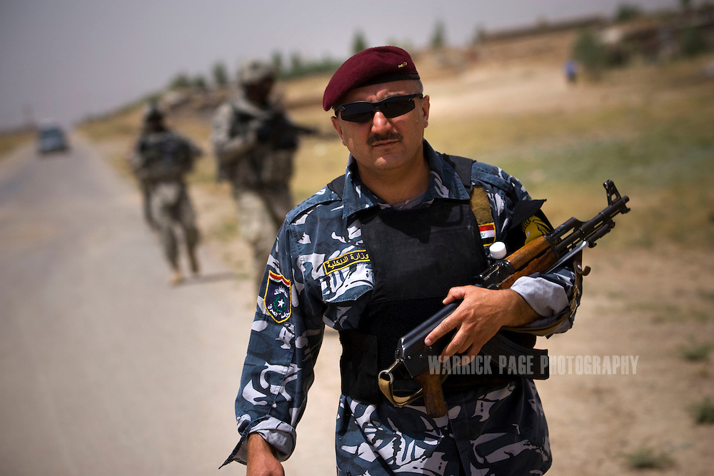 AL HAMDANIYAH, IRAQ - JUNE 03: An Iraqi policeman participates in a tri-partite humanitarian mission with US and Kurdish forces in a local village, on June 3 , 2010, in Al Hamdaniyah, east of Mosul, Iraq. Iraq faces multiple challenges in the lead-up to the drawn-down of US forces in Iraq, with many observers claiming that while they have the capablities of handling home-grown problems, they are far from being able to tackle external threats. Political wrangling has reportedly fostered greater instability throughout the country with fears of renewed sectarian violence breaking out as insurgents set-up attacks in an attempt to exploit vulnerabilities amongst the populace. (Photo by Warrick Page)