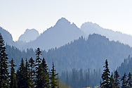 Lane and Waypenayo Peaks in the Tatoosh Range partially obscurred by wildlfire smoke in Paradise Valley.  Photographed from Mount Rainier National Park in Washington State, USA.