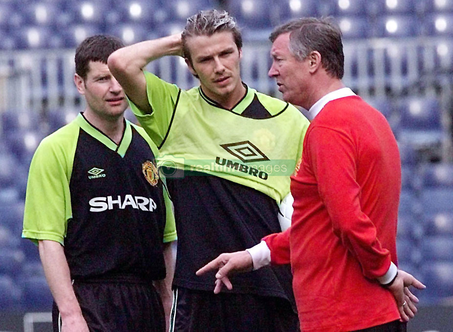 This picture can only be used within the context of an editorial feature. Manchester United manager Alex Ferguson talks tactics with David Beckham and Denis Irwin (left) at their teams training session at the Nou Camp stadium in Barcelona.