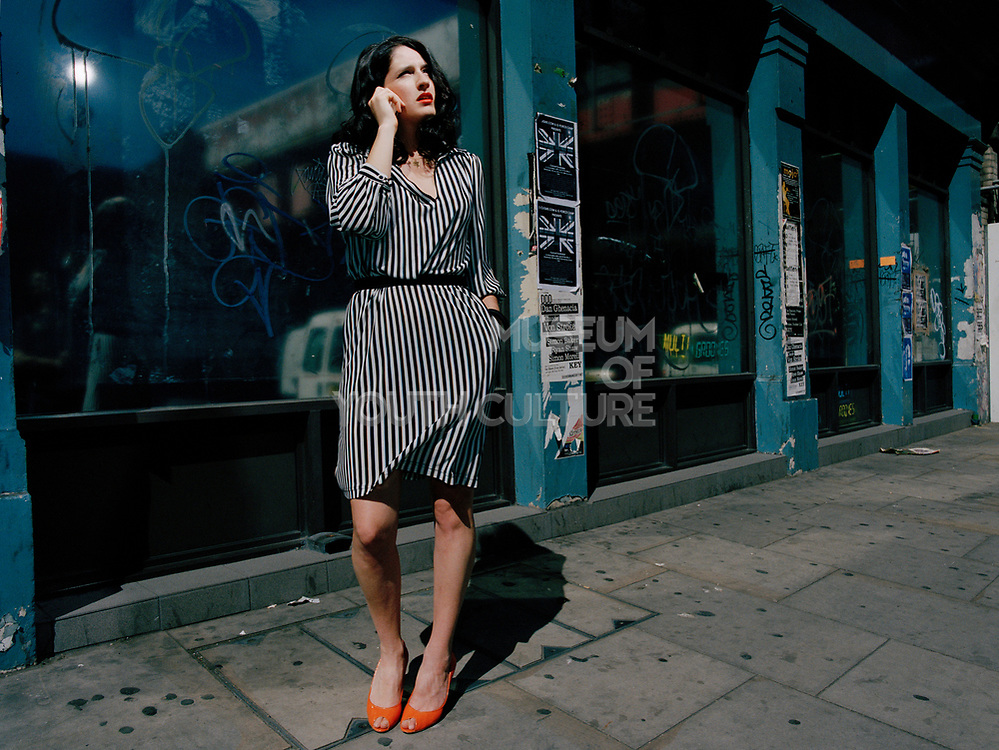Young woman in striped dress standing on pavement.
