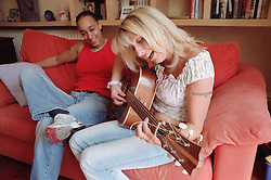Woman sitting next to partner on sofa listening to her playing guitar and singing,