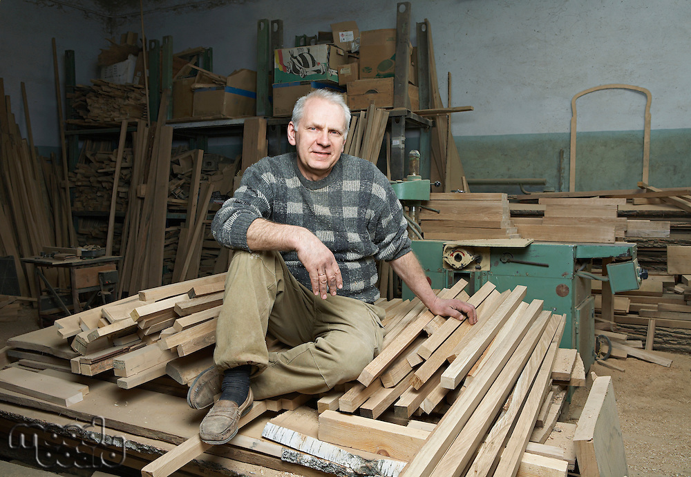 Carpenter Sitting on Wood Stacked in Workshop