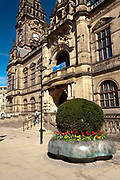 Sheffield Town Hall front facade and clock tower with colourful red Spring flowers, from Pinstone Street