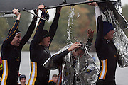 Sam Weiner's (middle) teammates; Greg Mariuzza (far left), Ander Beckham (left), and Brad Gerber (right), laugh as he gets drenched with water after their race.  Rowers had 90 seconds to get their boats out of the water and off the docks at the Finish Area Launch Site near the Harvard Weld Boathouse during the Head of the Charles Regatta...Photo by Kate Samp