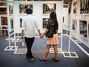 19 JULY 2013 - BANGKOK, THAILAND: People look at photos hanging in a photo exhibit in CentralWorld in Bangkok. The US Embassy in Bangkok sponsored the photo exhibit, which celebrates 180 years of US-Thai diplomatic relations. There are 180 photos hanging in the show, 90 by American photographers in Thailand and 90 by Thai photographers in the United States. The show, which opened July 19, is hanging in CentralWorld, a large mall in Bangkok, and is touring Thailand when it concludes its Bangkok run on July 21.     PHOTO BY JACK KURTZ