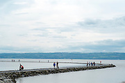 © Licensed to London News Pictures. 12/07/2014. West Kirby, UK People walk along the beach and paddle in the receding tide waters at West Kirby, Wirral, today 12th July 2014.  Photo credit : Stephen Simpson/LNP
