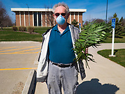 """05 APRIL 2020 - DES MOINES, IOWA:  A parishioner of Luther Memorial Church walks home after picking up palms at a drive through Palm Sunday service sponsored by Luther Memorial Church on the campus of Grand View University in Des Moines. About 150 people attended the service. They remained in their cars while the ministers read a short passage from the Bible, handed out palms and blessed them. On Sunday, 05 April, Iowa reported 868 confirmed cases of the Novel Coronavirus (SARS-CoV-2) and COVID-19. There have been 22 deaths attributed to COVID-19 in Iowa. Restaurants, bars, movie theaters, places that draw crowds are closed until 30 April. The Governor has not ordered """"shelter in place"""" but several Mayors, including the Mayor of Des Moines, have asked residents to stay in their homes for all but essential needs. People are being encouraged to practice """"social distancing"""" and many businesses are requiring or encouraging employees to telecommute.       PHOTO BY JACK KURTZ"""