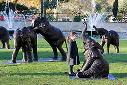© Licensed to London News Pictures. 04/12/2019. London, UK. 4 years old Georgiana Chubb from Hampden Gurney Primary School looks at a sculpture of an elephant in at Marble Arch during an unveiling of life-sized herd of 21 bronze elephants.<br /> The sculpture is the largest such depictionof an elephant herd in the world and is intended to draw attention to the plight of this species that could be extinct on current trends, by 2040. Each elephant in the sculpture is modelled after a real orphaned animal currently in the care of the Sheldrick Wildlife Trust. Left behind by poachers and other sources of human-wildlife conflict these animals have been raised by the trust in an effort to secure the future of the species. The herd will be displayed until 4 December 2020. Photo credit: Dinendra Haria/LNP