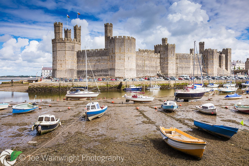 Caernarfon Castle, Gwynedd, North Wales, with pleasure boats resting on the bed of the River Seiont at low tide.