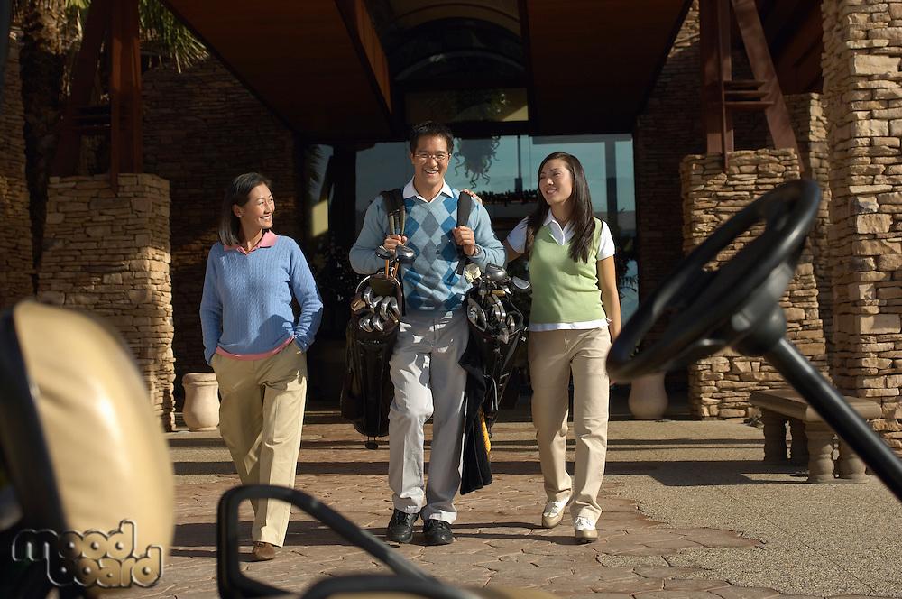 Man Carrying Girlfriend's Golf Clubs to Golf Cart