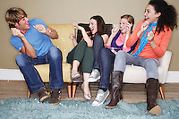 Young women throwing popcorn at friend on sofa