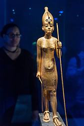 "© Licensed to London News Pictures. 01/11/2019. LONDON, UK. A woman views ""Wooden Statue of the King in the White Crown"".  Preview of ""Tutankhamun, Treasures of the Golden Pharoah"" at the Saatchi Gallery in Chelsea.  The exhibition celebrates the 100th year anniversary of the opening of Tutankhamun's tomb and displays 150 works in the largest collection of Tutankhamun's treasures ever to leave Egypt.  The show runs 2 November to 3 May 2020.  Photo credit: Stephen Chung/LNP"