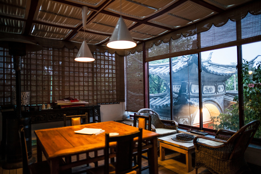 A small sitting room with traditional decor in Ye Yongqing's home in Dali City, China. Through the window is a view to the traditional entrance gate of the home.