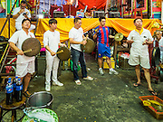04 OCTOBER 2016 - BANGKOK, THAILAND:  Thai Chinese men participate in a traditional cymbal playing circle in front of the Chinese opera stage at the Vegetarian Festival at the Chit Sia Ma Chinese shrine in Bangkok. The Vegetarian Festival is celebrated throughout Thailand. It is the Thai version of the The Nine Emperor Gods Festival, a nine-day Taoist celebration beginning on the eve of 9th lunar month of the Chinese calendar. During a period of nine days, those who are participating in the festival dress all in white and abstain from eating meat, poultry, seafood, and dairy products. Vendors and proprietors of restaurants indicate that vegetarian food is for sale by putting a yellow flag out with Thai characters for meatless written on it in red.    PHOTO BY JACK KURTZ