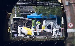 © Licensed to London News Pictures. 09/11/2016. London, UK. Members of an investigation team carry unidentified objects from the scene where a tram derailed near Sandilands tram station in Croydon, Greater London. Dozens of people are believed to be injured with emergency services saying that there has been a number of fatalities . Photo credit: Peter Macdiarmid/LNP