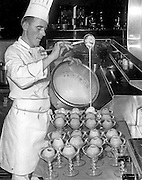 Pat LaFave, Chef of the Camlin Hotel and Cabanas, working in the Cloud Room Kitchen, poured Sabayon Sauce over apples that had been poached in sherry wine. (Bruce McKim / The Seattle Times, 1967)