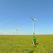 A man walking by a at the Ballywater Wind Farm, located between the villages of Kilmuckridge and Ballygarrett in County Wexford, Ireland. In recent years Ireland have seen a marked increase in the level of wind energy production. Today, wind farms in Ireland supply enough clean green power to support over 146,000 users.