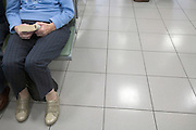 elderly female person reading a book while waiting at an airport