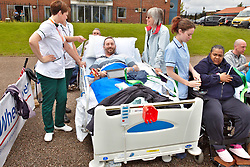 © Licensed to London News Pictures.  09/07/2012. STOKE MANDEVILLE, UK.  Jonathon Green (pictured in bed),  a patient at the nearby hospital, waits for the Olympic Torch to enter Stoke Mandeville Stadium, birthplace of the Paraolympics. Photo credit: Cliff Hide/LNP