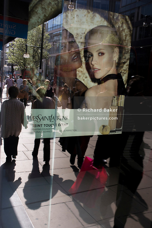 As shoppers pass-by, a shop poster for Yves Saint Laurent looks out from the window on Oxford Street, in London's West End.